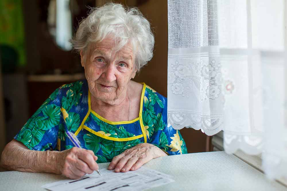Pensioner completing form writing